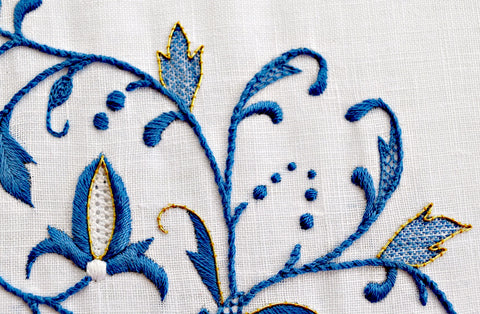 Closeup of Broiderie Stitch logo - French floral motif worked in blue, white, and golden threads.