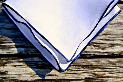 White linen handkerchief edged with navy satin piping