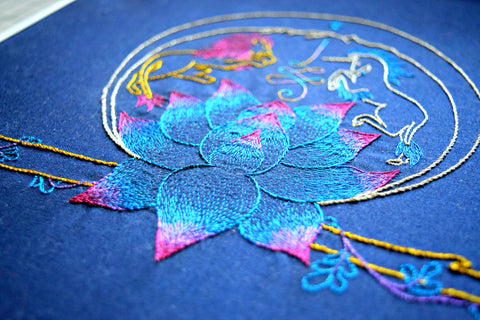 Embroidered design with lion, unicorn, and lotus in metallic thread on navy background