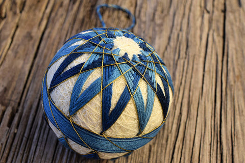 Closeup of blue temari on wooden background