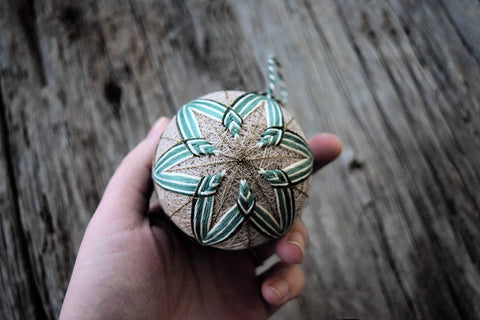 Green and white striped temari ball in hand