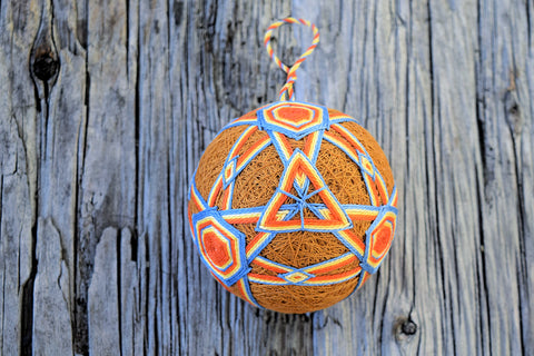 Japanese temari ball in orange and blue on wood background