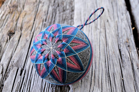 Pink and blue temari ball ornament with kiku design on wood ground