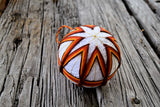 Harvest colored temari ball on wood background