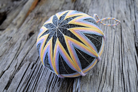 Closeup of temari hand embroidered in pastels on grey