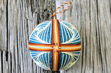 Embroidered temari ball with brown interlaced bands and cream swirl pattern on blue base