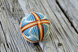Brown and cream design embroidered on teal blue temari ball