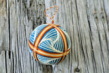 Closeup of cream swirl design on brown and teal temari ball