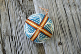 Japanese temari ball embroidered in warm brown and cream on teal base