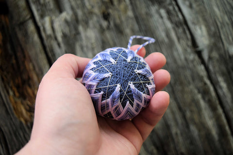 Small six-pointed star temari ball held in woman's hand
