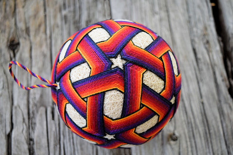 Embroidered temari ball with vibrant bands interlacing to form stars in colors from yellow to deep blue
