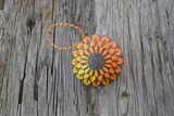 Top down view of temari hand embroidered in bright yellows and oranges on slate grey base