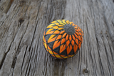 Japanese temari ball embroidered in warm yellows and oranges shading from one side to the other across the mari