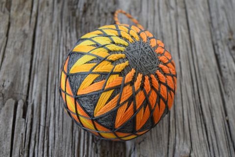Side view of yellow, orange, and grey temari showing kiku design and shaded obi band