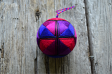 Japanese kousa temari ball stitched in red, purple, blue on wood background