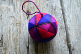 Hand embroidered temari ball in jewel tones with twisted thread hanger.