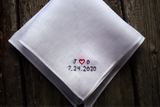 White linen pocket square on wood background embroidered with initials and wedding date