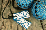 Close up of premium loop embroidered poi handles with teal and silver arabesques