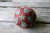 Grey temari ball hand embroidered with glowing red and yellow stars