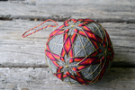 Close up of hand embroidered temari ball with red and brown stars interlocking to form diamonds