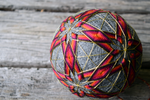 Closeup of japanese temari ball showing metallic threads and sunset colored stars