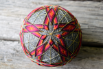 Centered image of star embroidered in warm tones on face of temari ball