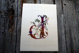 Hand embroidered ornate letter J in red and blue silk with goldwork accents