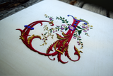 Closeup of hand embroidered monogram in red silk showing goldwork details