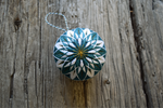 Front view of teal and white temari embroidered in star pattern with golden accents
