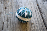 Teal and white Japanese temari with golden accents on obi band