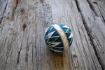 Japanese temari ball embroidered in teal, white, and gold