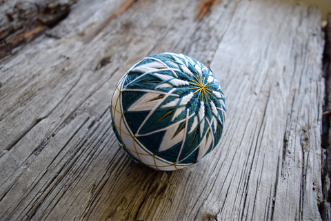 Closeup of temari ball worked in teal and white with gold marking threads