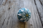 Japanese temari ball embroidered in teal and white kiku design with gold accents