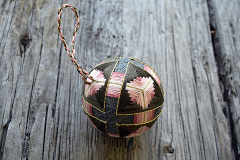 Closeup of hand embroidered temari ball in soft rose and grey browns with twisted thread hanger