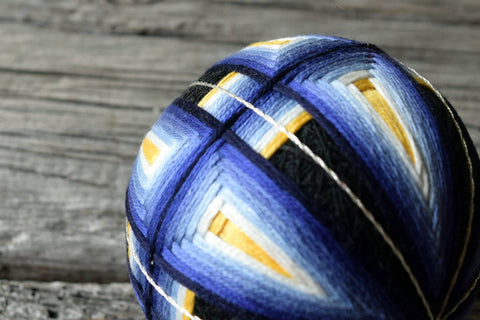 Close up of blue and yellow temari ball showing interweaving and silver threads