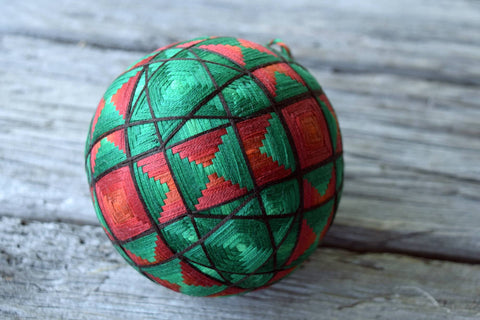 Hand embroidered Japanese temari ball in emerald green and copper brown with all over interlacing pattern