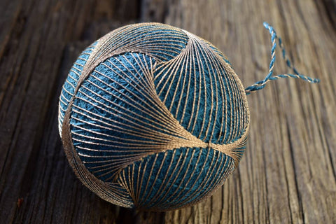 Japanese temari ball with swirl design in brown on blue base