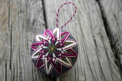 Japanese temari ball embroidered in kiku pattern in plum and white on grey