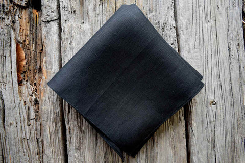 Black Irish linen pocket square on wood background