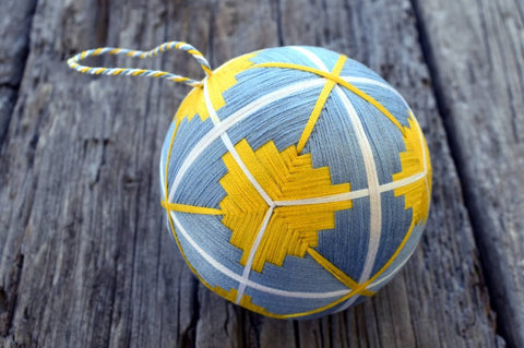 Embroidered temari ball in shades of sky blue and bright yellow with white accents