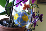 Blue, yellow, and white temari ball nestled among purple orchids in a window