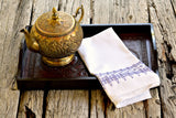 Huck tea towel embroidered in shades of purple on tray with brass teapot