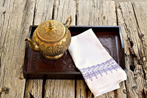 White huck kitchen towel embroidered with filigree design in shades of lavender on tray with Moroccan teapot
