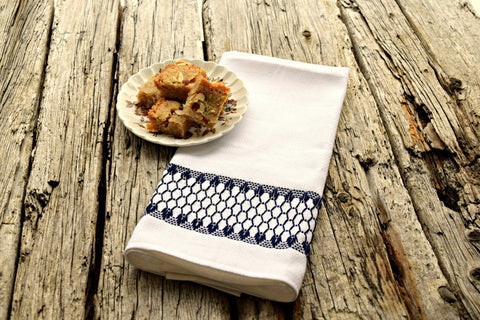 Kitchen tea towel in white huck embroidered with a band of navy diamonds