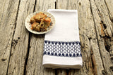 Huck tea towel hand embroidered in navy with plate of cookies