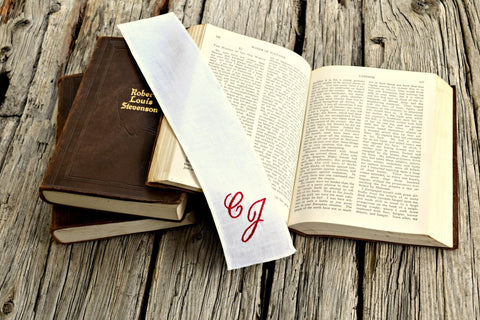 White linen bookmark personalized with monogrammed initials across open book