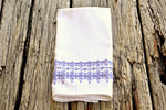 White huck kitchen towel embroidered in soft purple