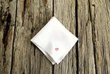 White linen handkerchief hand embroidered with tiny red heart