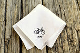 White linen handkerchief embroidered with small bicycle silhouette and the initials MMS in black