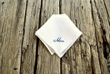 White linen hanky embroidered with Mrs. on wood background